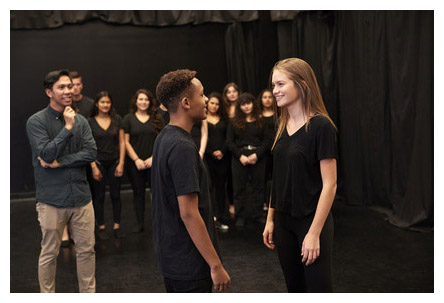 adjunct teacher working with students on a play