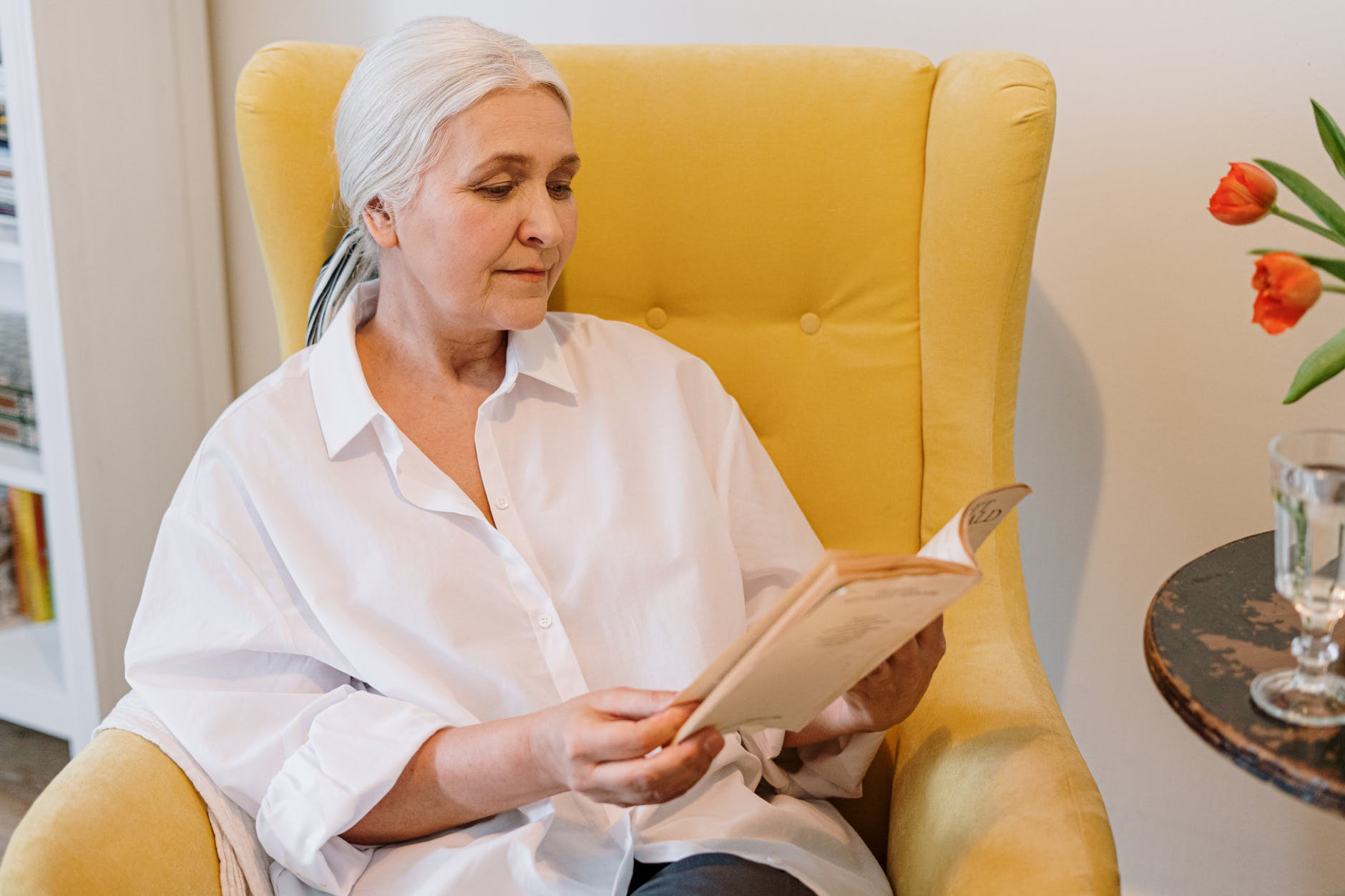 an elderly woman sitting on a couch reading a poetry book