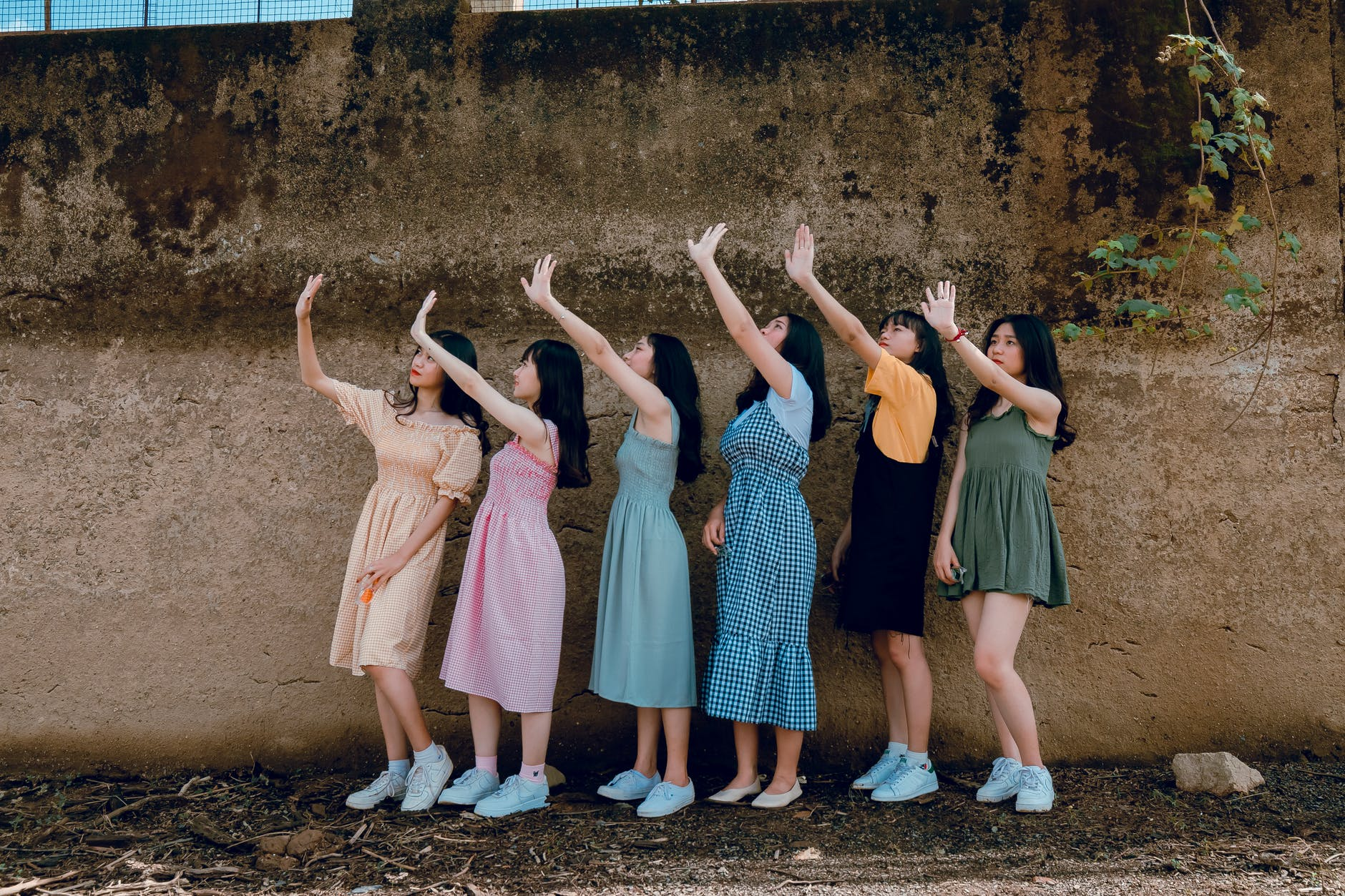 group of women standing infront of brown wall